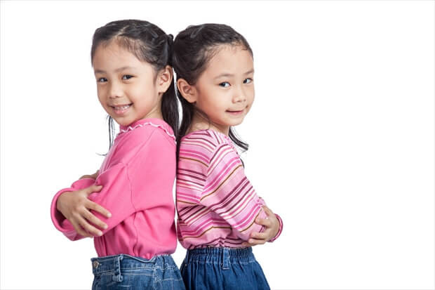 Asian twin sisters fold arms  standing back to back