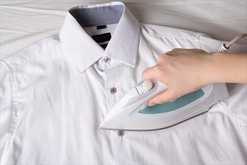 female hand with iron ironing white cotton shirt