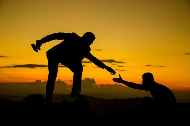 Businessman gived hand for pull team to peak of  mountain for work together.