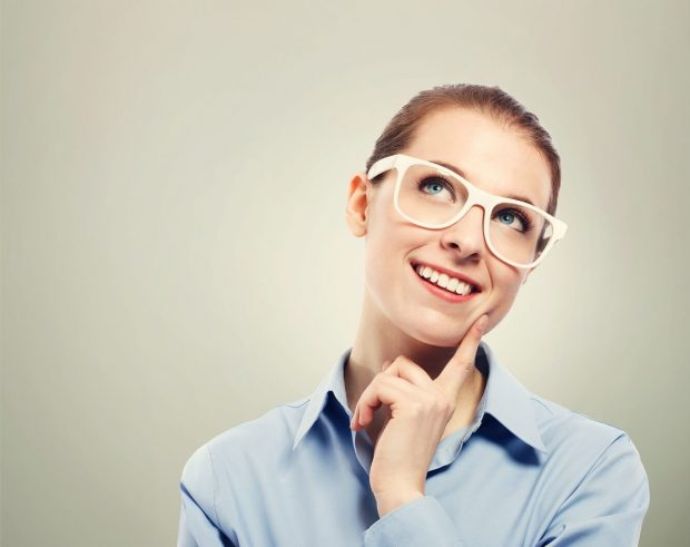Thinking business woman wearing white eyeglasses
