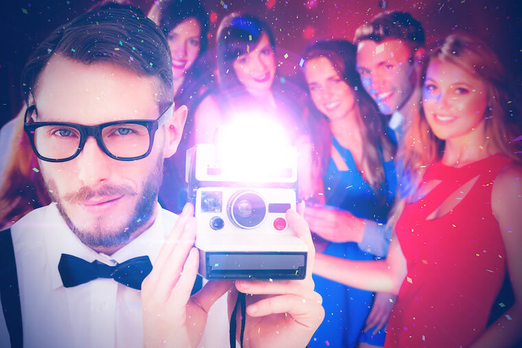 Geeky hipster holding a retro camera against happy friends on a night out together
