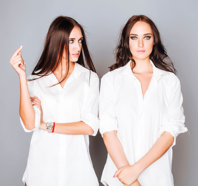 two sisters twins posing, making photo selfie, dressed same white shirt, diverse hairstyle