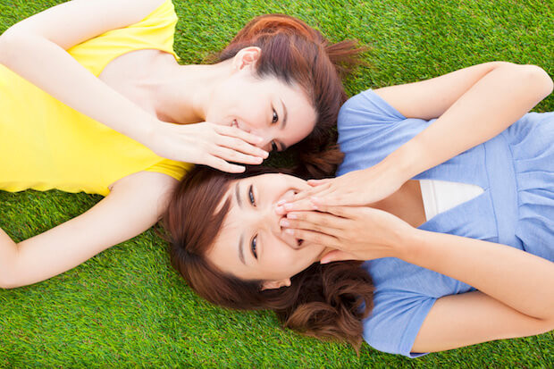 two asian sisters whispering gossip on the grass