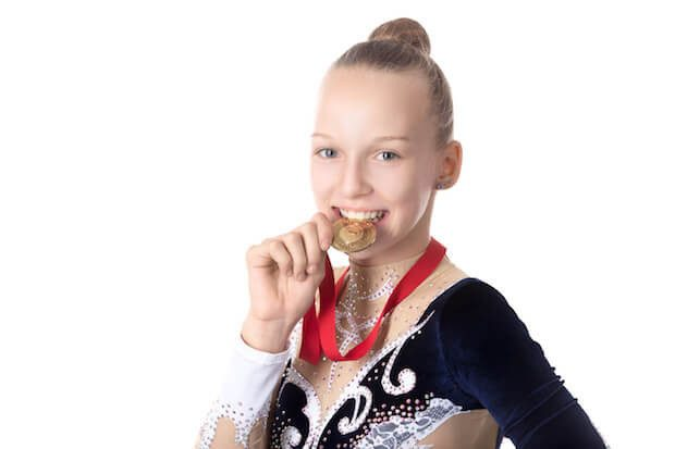 Gymnast girl biting her award medal