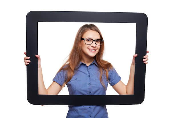 Smiling female peeping out of tablet frame