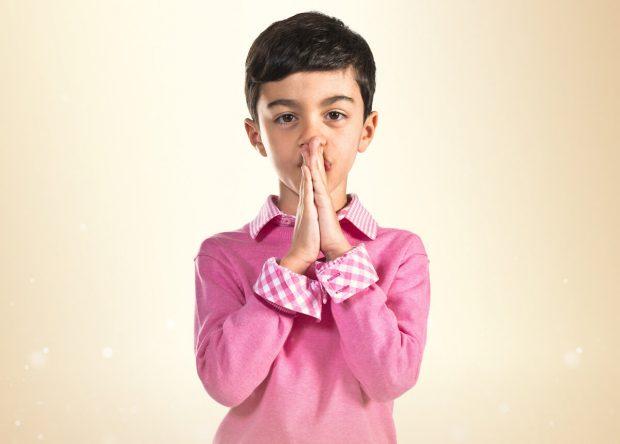 Boy pleading over white background