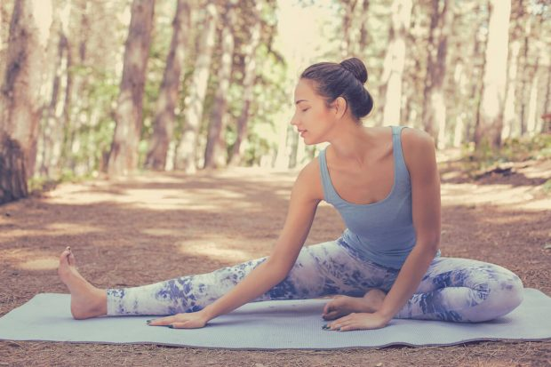 Stretching woman in outdoor exercise smiling happy doing yoga